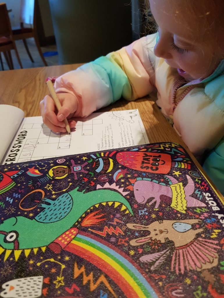 Her very first crossword in her My Busy Bots activity pack
