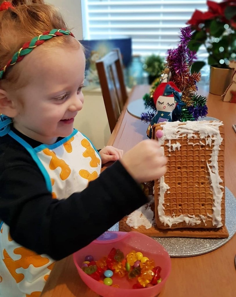 Decorating her gingerbread house