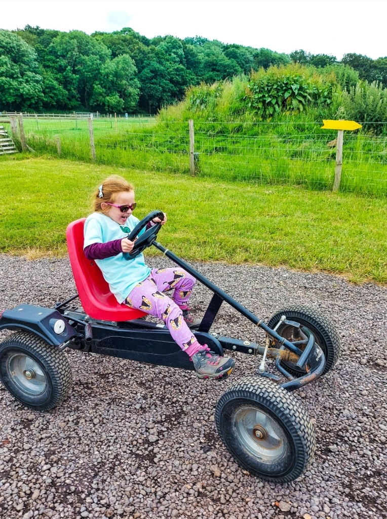 Riding the Go Karts - her legs only just reached but she loved them!